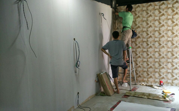 Inspection By One Of The Installer When Installing Wallpaper At Corner Wall
